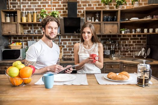 Young couple using digital tablet while having breakfast at kitchen table