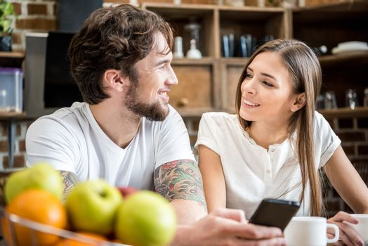 Young couple using smartphone while having breakfast at kitchen