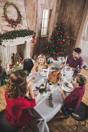 High angle view of happy family sitting at holiday table at Christmas time