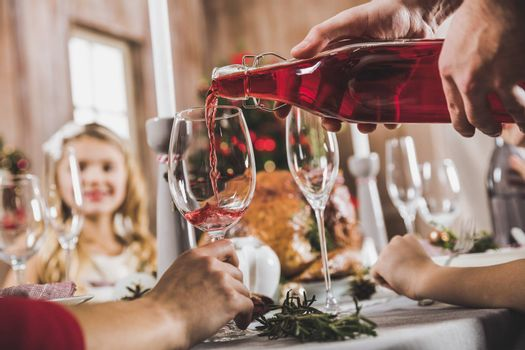 Close-up partial view of man pouring wine in glass at Christmas eve