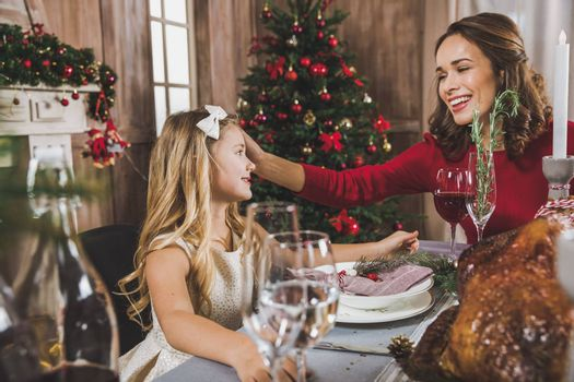 Happy mother and daughter sitting at holiday table at Christmas time
