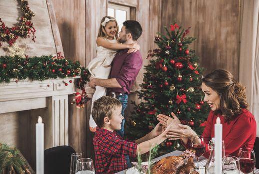 Happy family having fun at holiday table at Christmas time