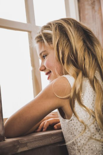 Cute smiling girl in glittering dress looking at window