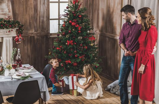 Smiling parents looking at children opening gift boxes near Christmas tree