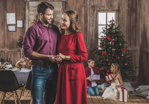 Smiling couple holding hands and looking at each other while children opening gift boxes near christmas tree