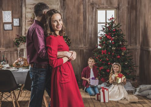 Smiling couple hugging while children opening gift boxes near christmas tree