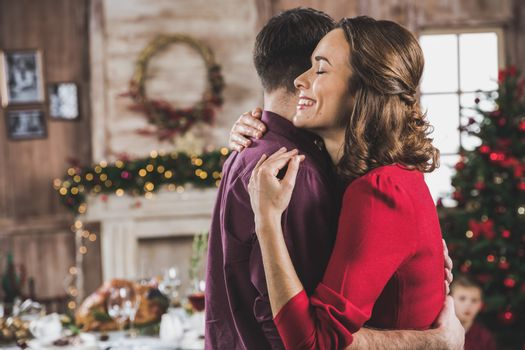 Portrait of beautiful smiling couple hugging at Christmas eve