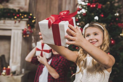 Cute children opening gift boxes on floor near Christmas tree