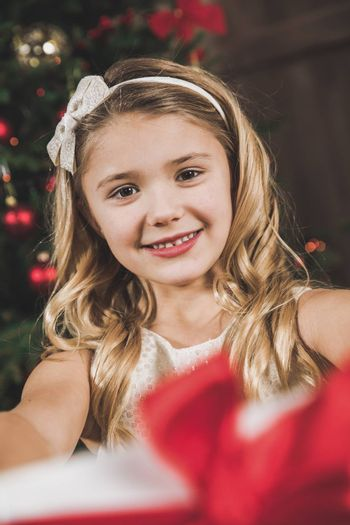 Cute smiling girl holding Christmas present and looking at camera