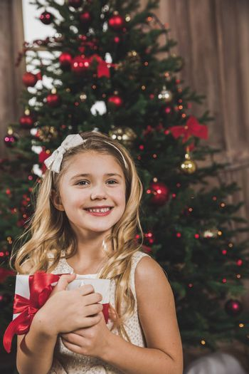 Cute smiling girl holding gift box near Christmas tree