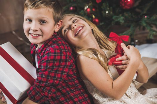 Cute happy siblings sitting near christmas tree and holding gift boxes