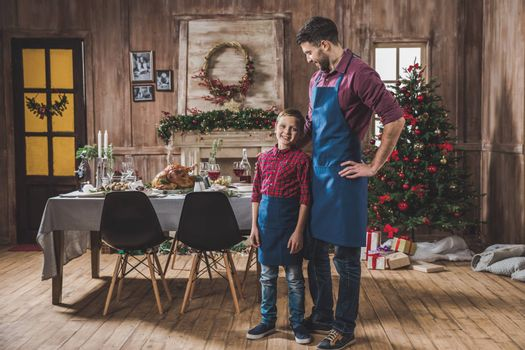 Happy father and son in blue aprons standing near Christmas table