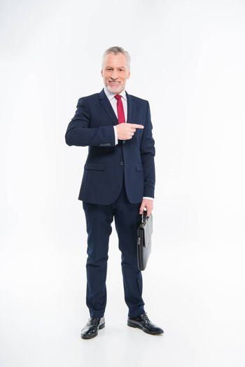 Smiling mature businessman holding briefcase and pointing away with finger