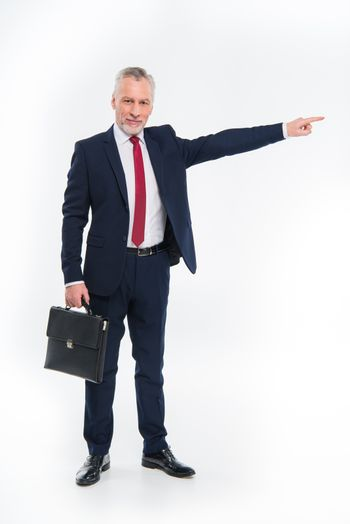 Smiling businessman holding briefcase and pointing away on white