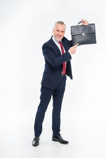 Smiling businessman pointing at briefcase on white