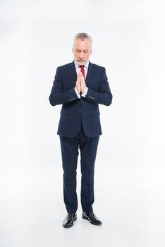 Full length portrait of mature businessman praying on white