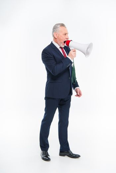 Handsome mature businessman shouting in loudspeaker on white