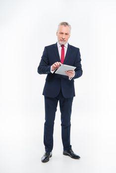 Mature businessman using digital tablet and looking at camera