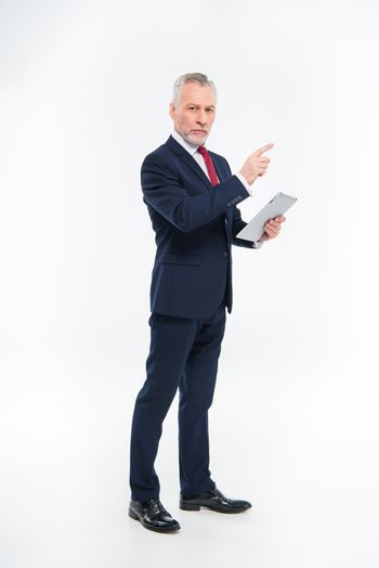 Serious businessman holding digital tablet and pointing with finger