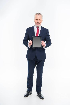 Full length portrait of businessman holding digital tablet and smiling at camera