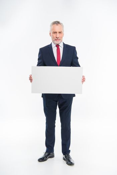 Businessman holding blank white card on white