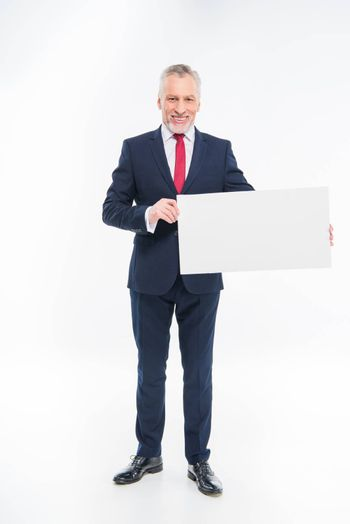 Handsome mature businessman holding blank card and looking at camera on white