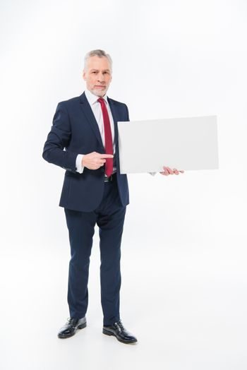 Handsome mature businessman holding blank card and pointing at copy space