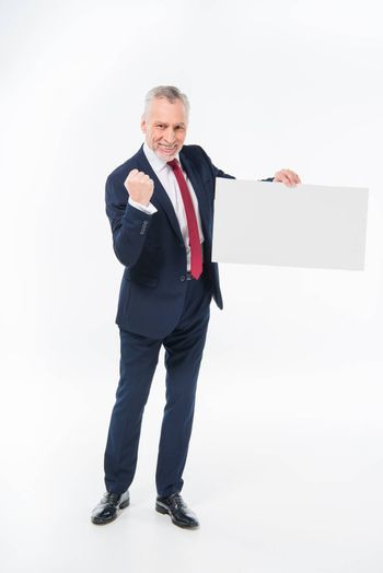 Excited mature businessman triumphing and holding blank white card