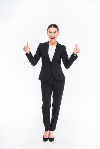 Attractive businesswoman in suit showing thumbs up and smiling at camera
