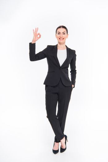 Smiling businesswoman showing OK sign and looking at camera on white