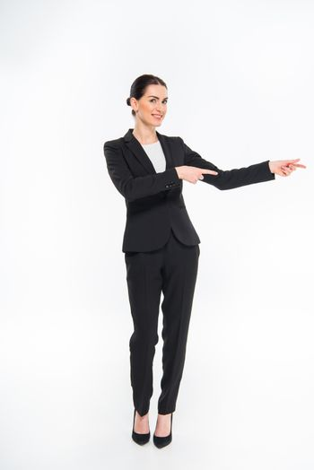 Smiling businesswoman pointing with fingers and looking at camera on white
