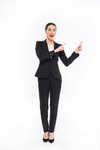 Shocked businesswoman pointing with fingers and looking at camera on white