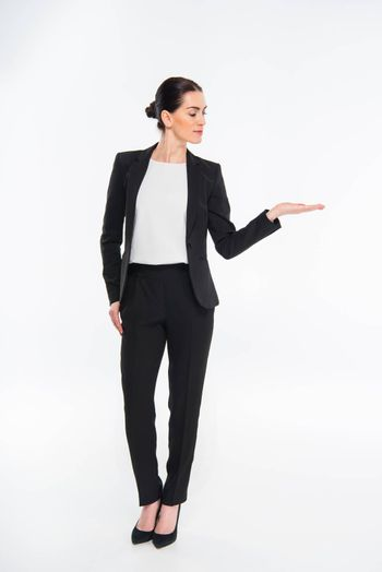 Attractive businesswoman looking at palm on white