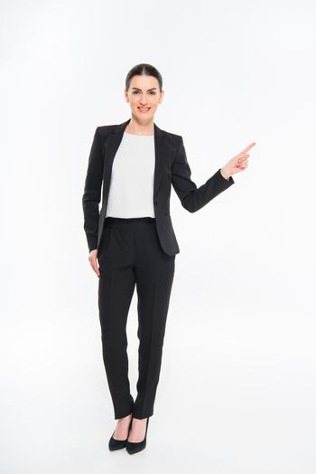 Smiling businesswoman pointing with finger and looking at camera on white