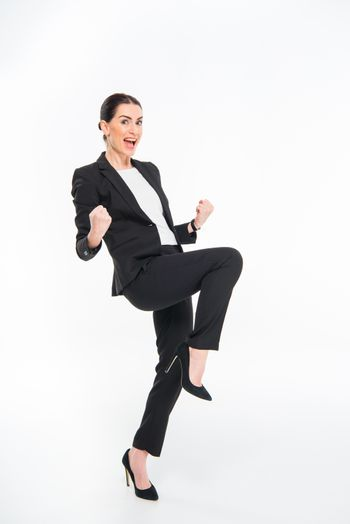 Cheerful businesswoman triumphing and looking at camera on white