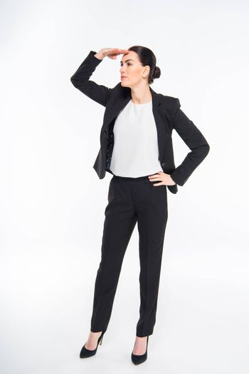 Attractive businesswoman with hand on forehead looking away on white