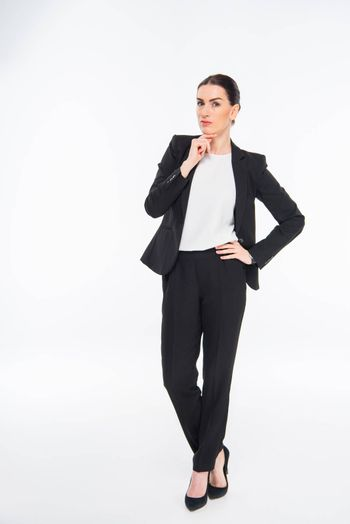 Attractive businesswoman with hand on chin looking at camera on white