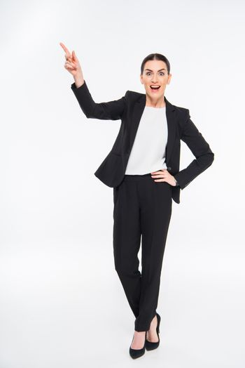 Surprised businesswoman pointing with finger and looking at camera on white