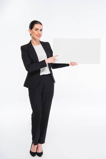 Smiling businesswoman holding blank white card and pointing at copy space
