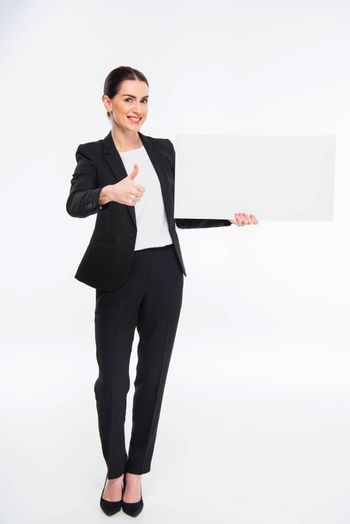 Smiling businesswoman holding blank card and showing thumb up