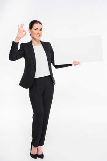 Smiling businesswoman holding blank white card and showing OK sign