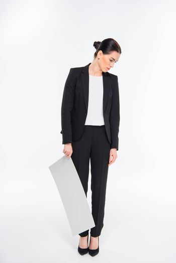 Tired businesswoman holding blank white card and looking down