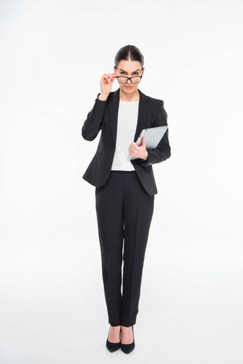 Attractive businesswoman holding digital tablet and eyeglasses on white