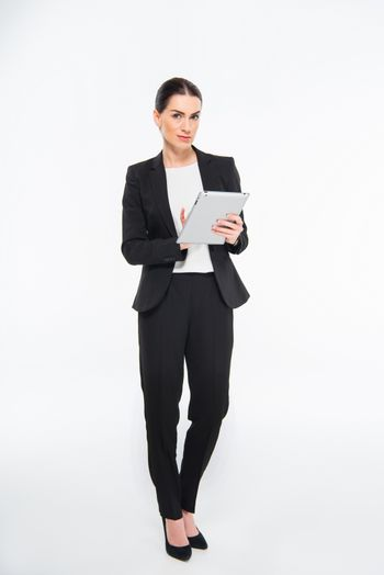 Businesswoman using digital tablet and smiling at camera on white