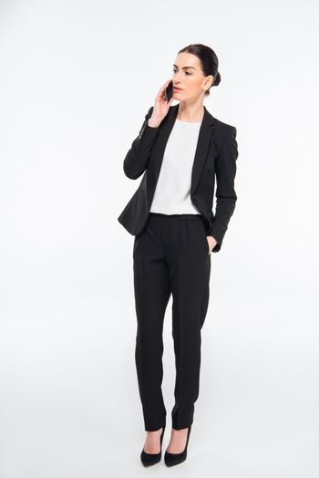 Serious young businesswoman talking on smartphone