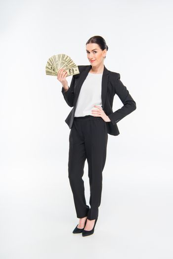 Smiling young businesswoman holding dollar banknotes on white