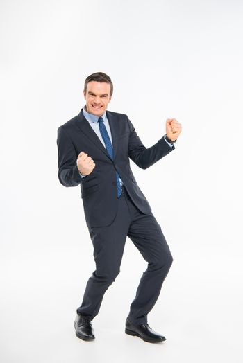 Cheerful businessman triumphing and looking at camera on white
