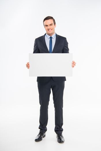 Smiling businessman holding blank white card and looking at camera