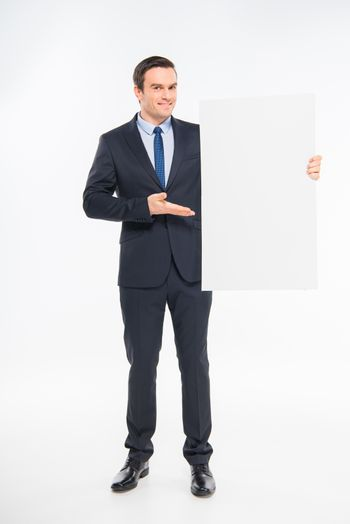 Smiling businessman holding blank white card and showing copy space