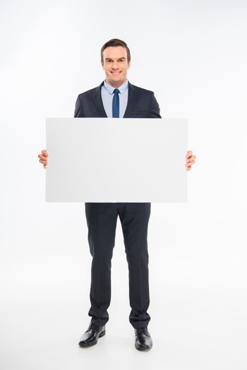 Smiling businessman holding blank card and looking at camera